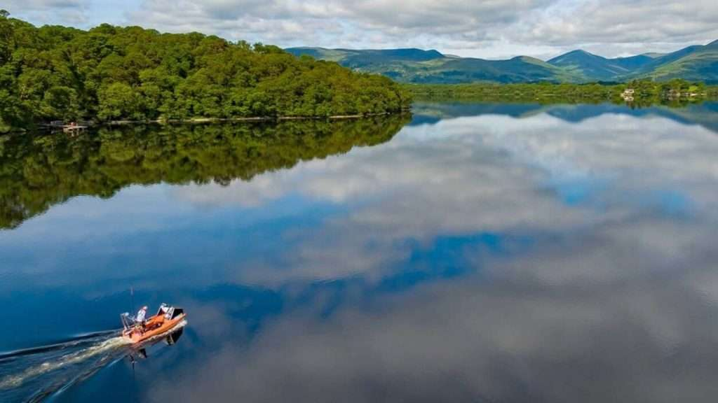 Boat on wthe ater with hills - activities around The Trossachs