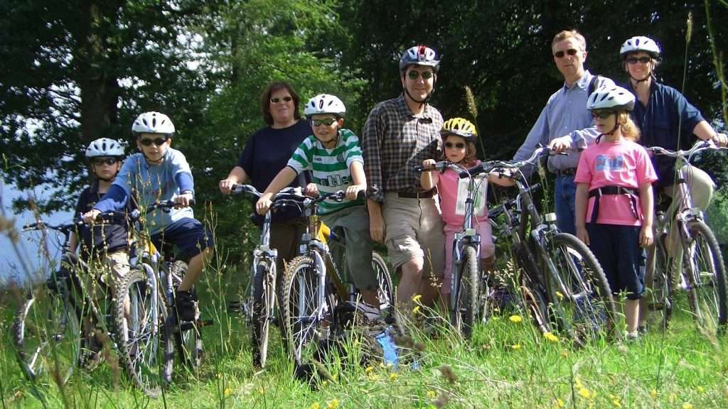 2 family groups of all ages stand with their bikes in the long grass