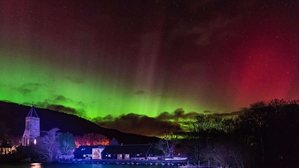 Aurora Borealis shimmers green and red and purple over the Lake of Menteith fisheries