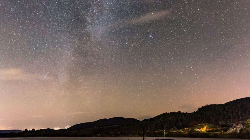 Night picture of the milky way above the dark Menteith hills
