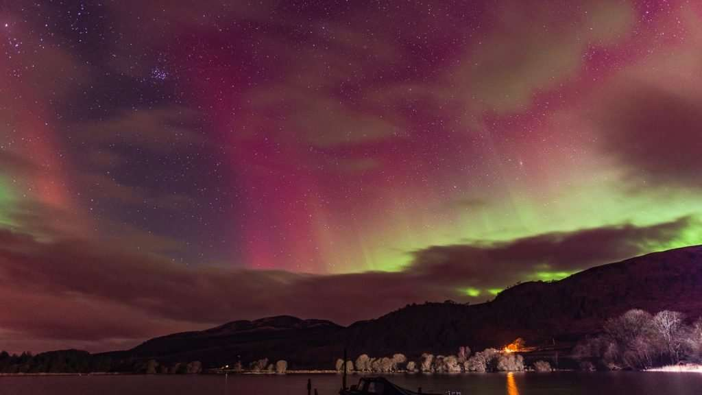 Aurora reds, greens, pinks and purple shimmer in the sky above the Menteith hills