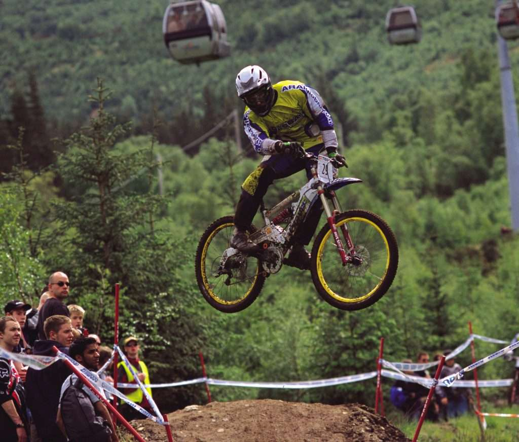A mountain biker, in the air after going over a jump