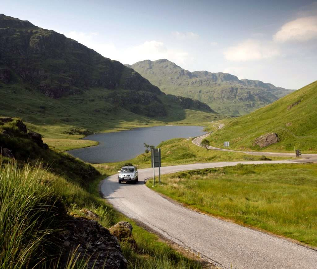 long wynding road with through mountains with loch ahead