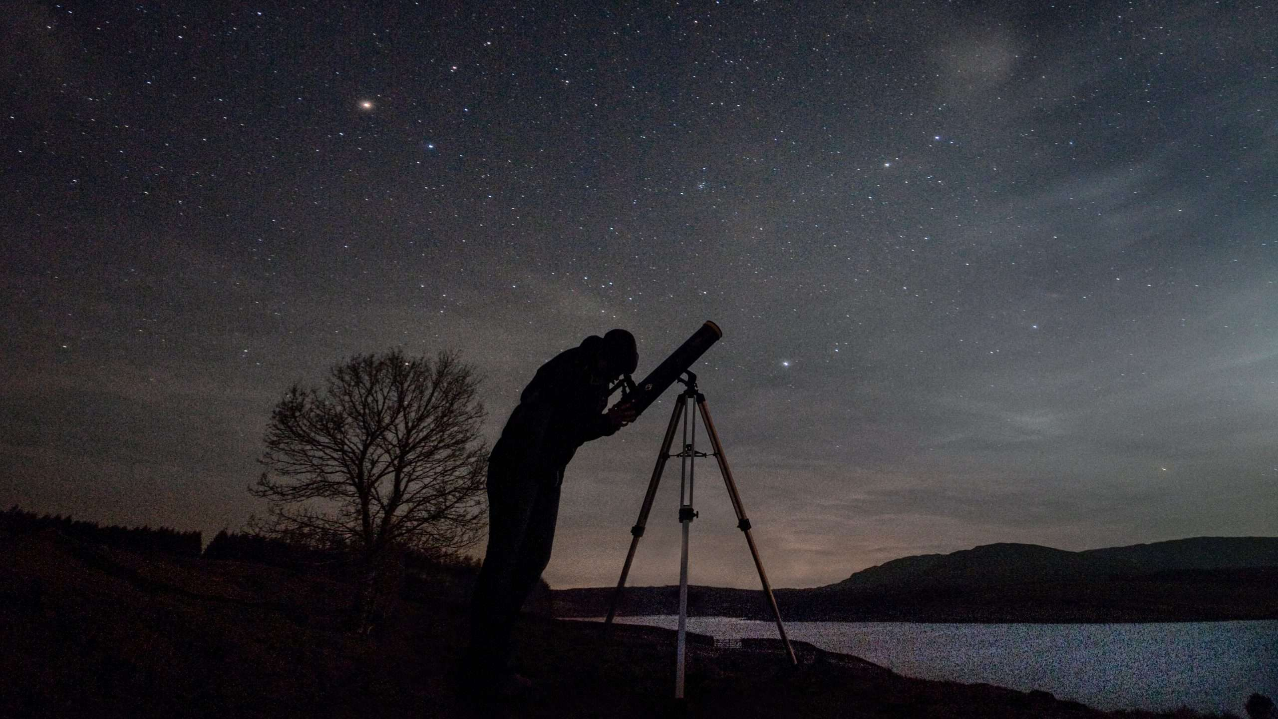 Man standing on the shore of a loch at night star gazing